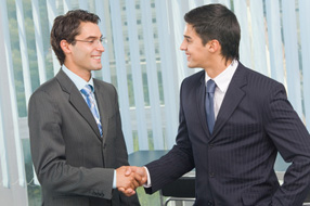 Two businesspeople cheering by handshake at office